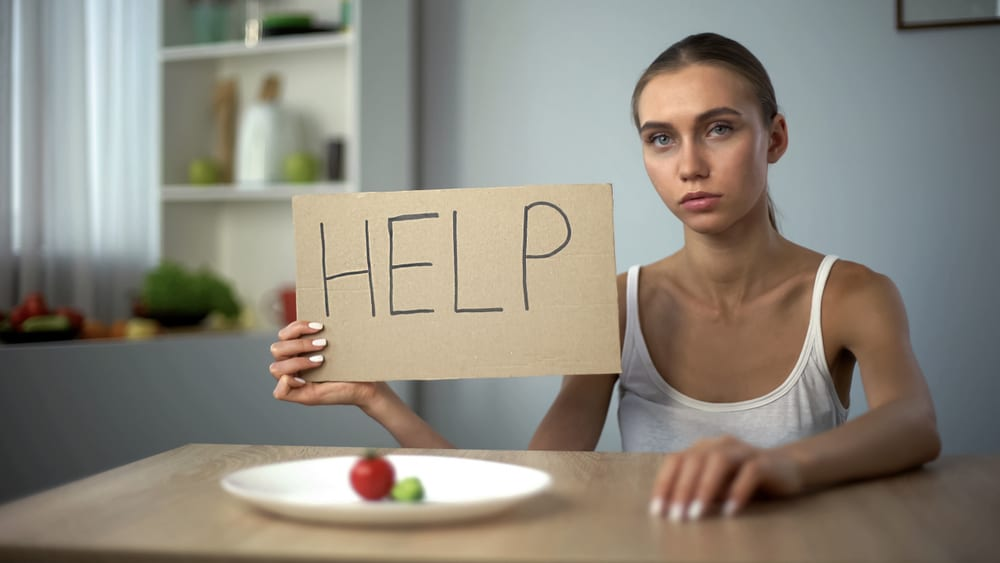 Young woman with anorexia asking for help and support with her eating disorder