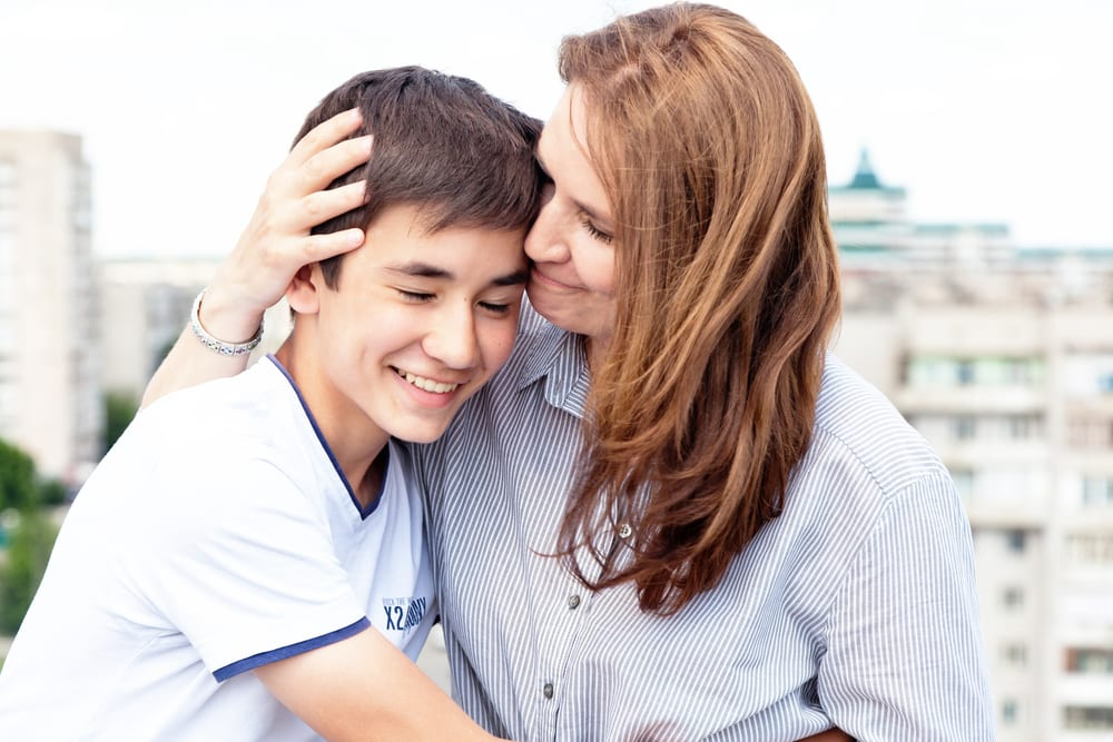 Mum and teenager with eating disorder hug during recovery